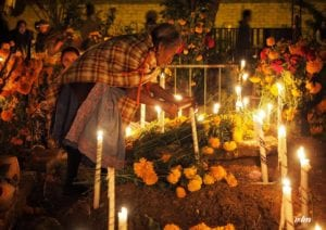 A local woman lights candles at a local indigenous cemetery