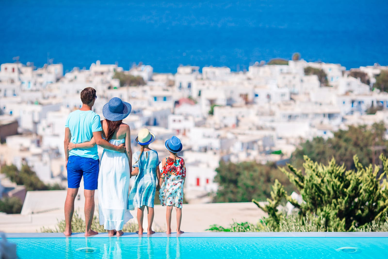 A family admiring a few from their pool looking out into the town.