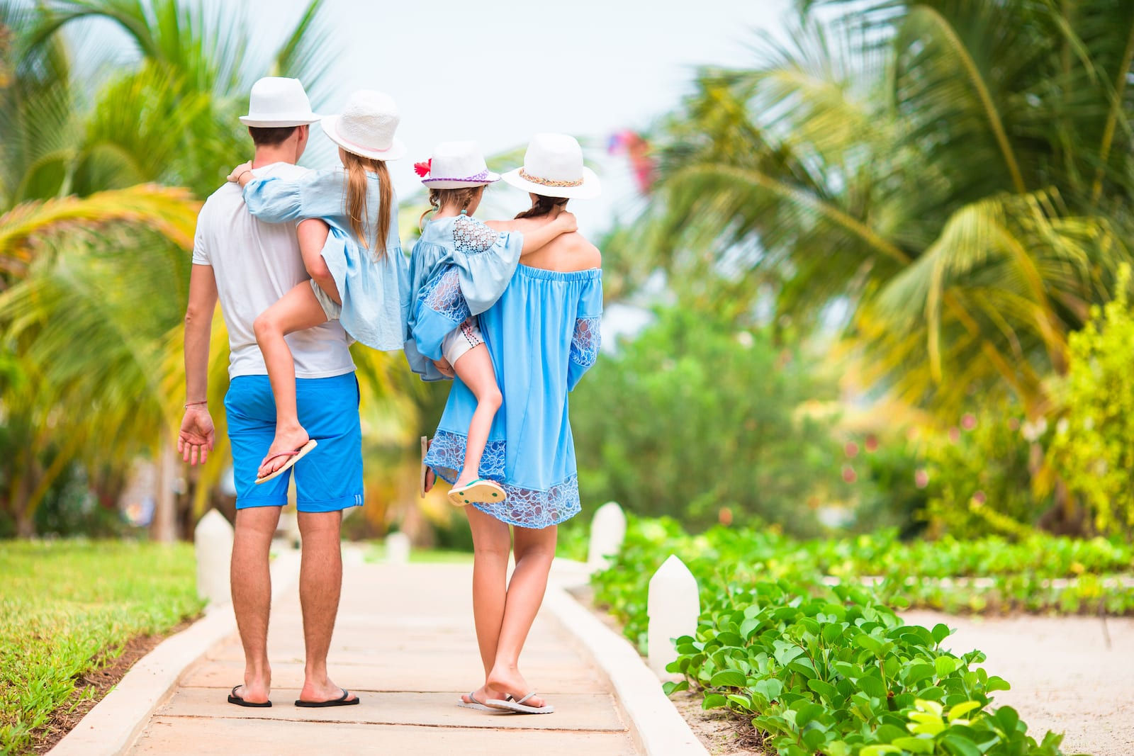 Parents carrying their kids walking at a caribbean resort.