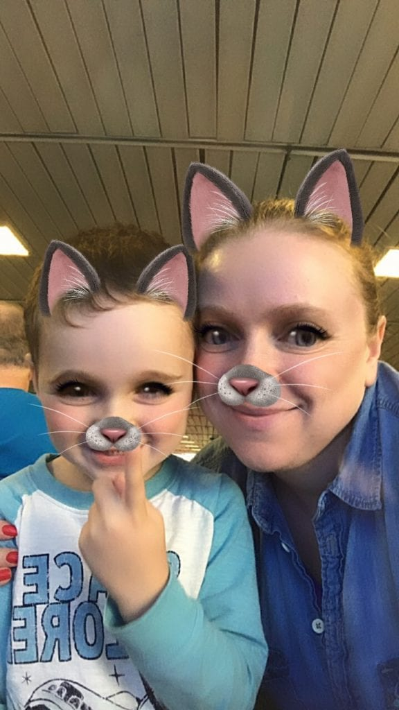 Travel agent and son posing for a silly selfie with a filter of a cat over their faces.