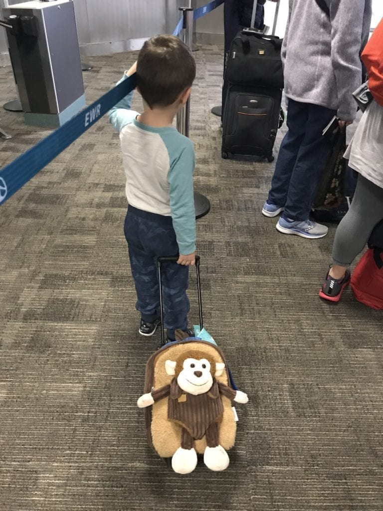 Travel agent's son with a wheeling suitcase waiting in line to board the airplane.