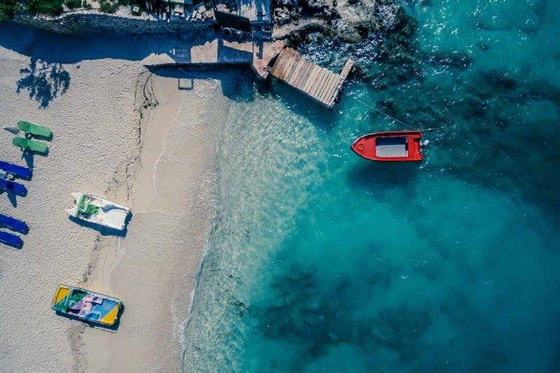 A bird's eye view of a red boat next to a boat dock at a Beach in Albania