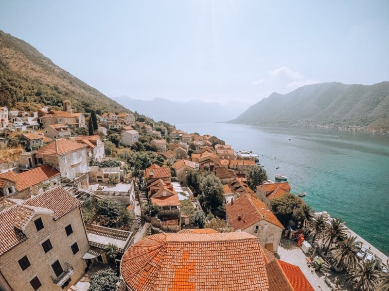A birds-eye view of the beautiful coast of Croatia with houses along the side of a mountain on the edge of the Adriatic Sea