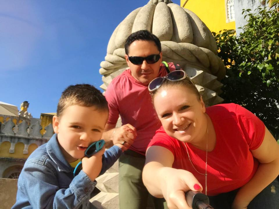 Family of three, enjoying beautiful day exploring - outside of Pena Palace in Sintra, Portugal