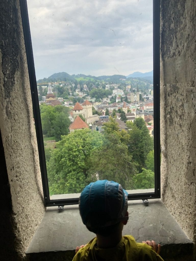A boy is looking from above at the old town of Lucerne, Switzerland