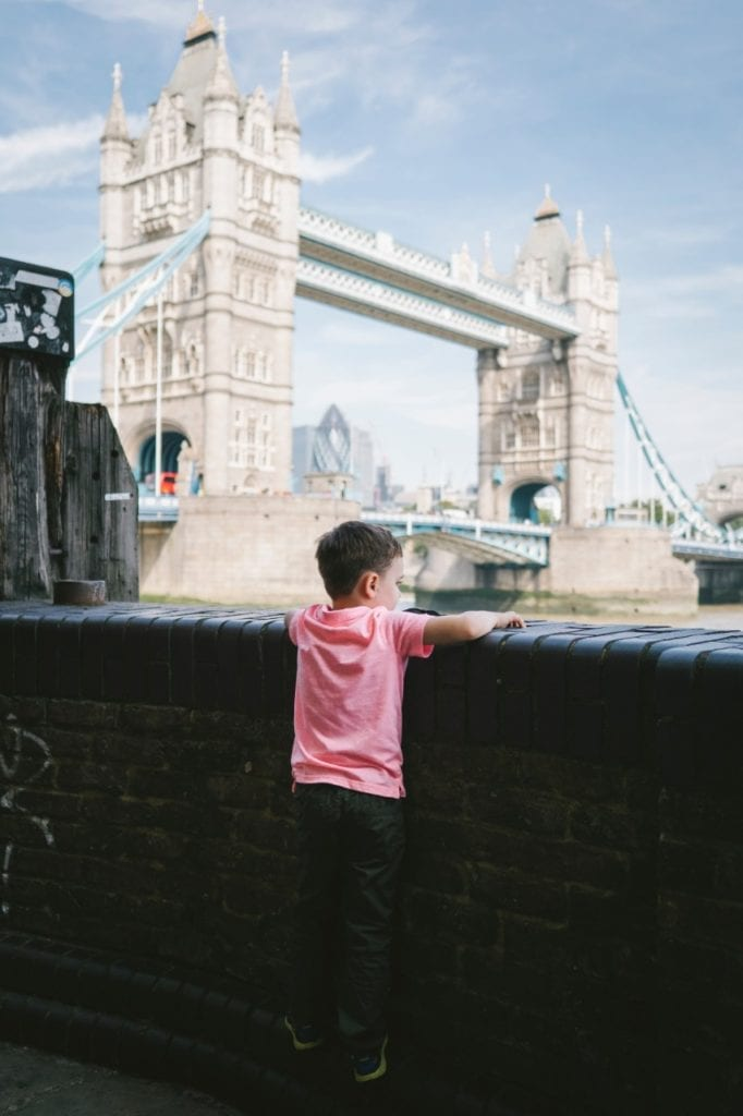 A boy looking at the Tower Bridge in London, England